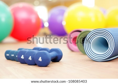 sporting dumb-bells balls and carpets lie on a background a sporting hall - stock photo