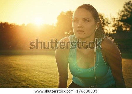 Sporting in the sunset / Vintage style photo from a young woman is tired after run - stock photo