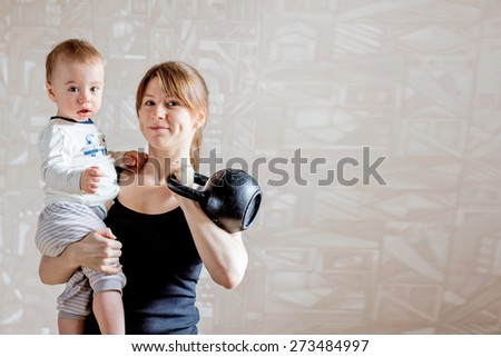 Sportive beautiful mother with baby and kettlebell in hands. Motherhood is not a cause to let oneself go - stock photo