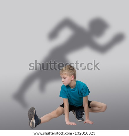 Sportive boy stretching his leg with runner's silhouette behind him - stock photo