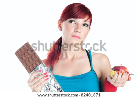 Sportive caucasian young woman choosing between sweets and diet, isolated on white - stock photo
