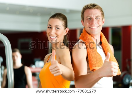 Sportive couple in gym or fitness club looking at the viewer - stock photo