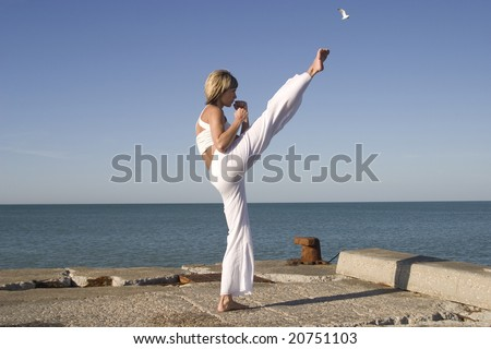 Sportive girl exercising next to the sea - stock photo