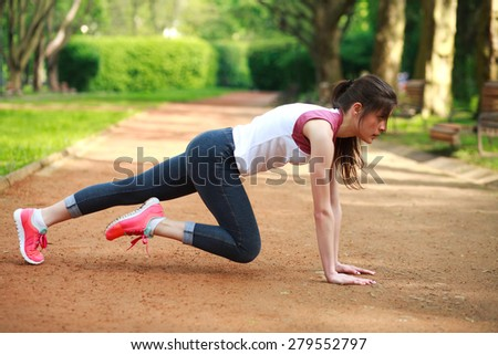 Sportive girl working out doing push ups press exercise in summer park  - stock photo