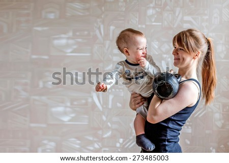 Sportive happy mother and son and kettlebell in hands. Motherhood is not a cause to let oneself go - stock photo