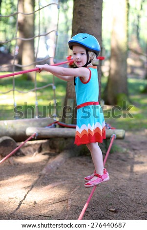 Sportive kids playing outdoors at summertime. Happy child, healthy toddler preschool age girl enjoying activity in a climbing adventure park on a summer day - stock photo