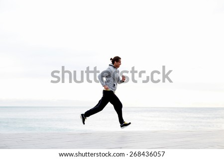 Sportive male runner working out outdoors jogging along seashore with beautiful sky horizon on background, jogger listening to music on smart phone while training outdoors - stock photo