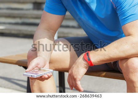 Sportive man sits on a bench and checks his fitness results on a smart phone. He wears a fitness tracker wristband on his left arm. - stock photo