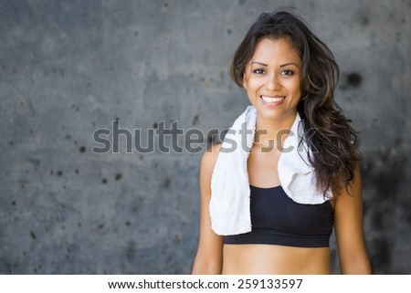 Sportive woman posing with a towel and a smile after workout - stock photo