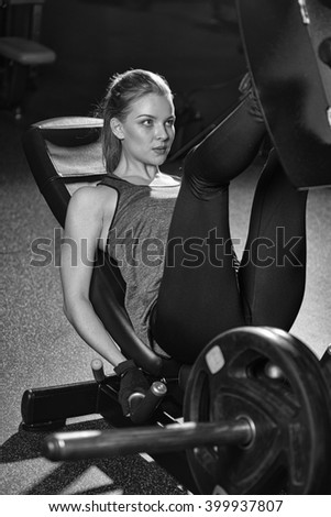 Sportive woman using weights press machine for legs. Gym. - stock photo
