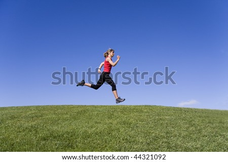 Sportive young women running on the nature - stock photo