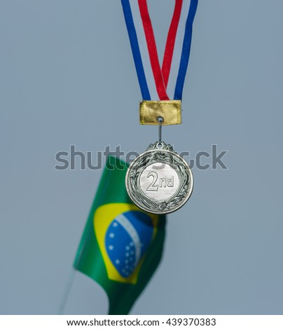 sports a silver medal and a Brazilian flag - stock photo