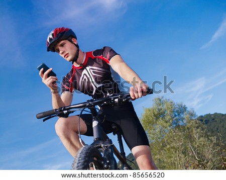 sports activity: young adult cyclist riding mountain bike and text messaging on cellphone. Horizontal shape, low angle view, copy space - stock photo
