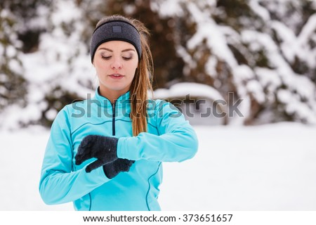 Sports and activities in winter time. Slim fit fitness woman outdoor. Athlete girl training wearing warm sporty clothes outside in cold snow weather. - stock photo