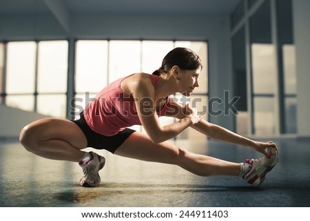 Sports background. Happy woman exercising at the gym - stock photo