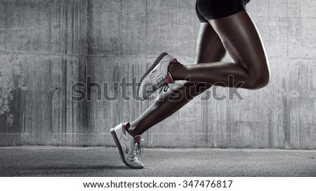 Sports background. Runner. Side view of a jogger legs on concrete wall - stock photo