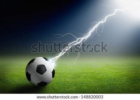 Sports background - soccer ball on green stadium struck by lightning, bright light from spotlight - stock photo