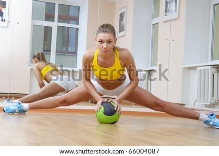 Sports blonde girl do the splits in gym - stock photo