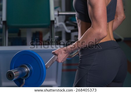 Sports, bodybuilding. Attractive woman in gym.Fitness in the gym. Strength training and beauty. Picture a strong woman. Blonde sexy girl fitness in sexy wear with perfect body posing in the gym. - stock photo