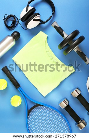 Sports equipment and T-shirt on color table, top view - stock photo