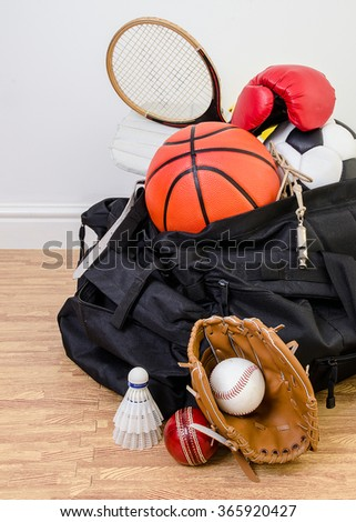 sports equipment in a holdall sports bag on a gym floor. football, baseball, cricket, basketball, boxing, badminton, squash. Portrait with copy space. - stock photo
