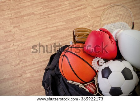 sports equipment in a holdall sports bag on a gym floor. football, rugby, baseball, cricket, basketball, boxing, badminton, squash. Landscape with copy space. - stock photo