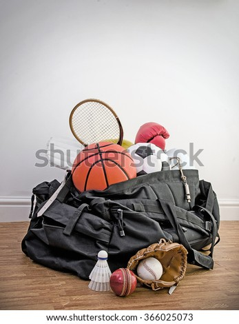 sports equipment in a holdall sports bag on a gym floor. football, rugby, baseball, cricket, basketball, boxing, badminton, squash. Portrait with copy space. - stock photo