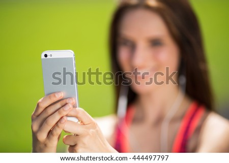 Sports girl with headphones sitting on the grass makes selfie - stock photo