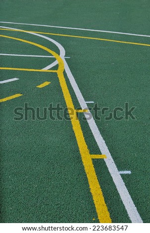 Sports ground made with gravel in green. Basketball lines in yellow and white - stock photo