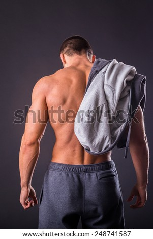 Sports guy in a tracksuit. A man in a sports jacket with a hood. The guy takes off her jacket and shows his muscular body. Fitness, strength, courage, a trained man. - stock photo