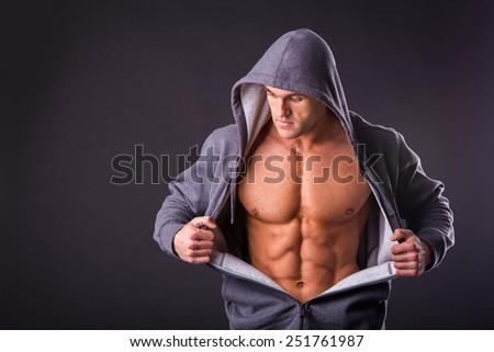 Sports guy in a tracksuit. A man in a sports jacket with a hood. The guy takes off his jacket and shows his muscular body. Fitness, strength, courage, a trained man. - stock photo