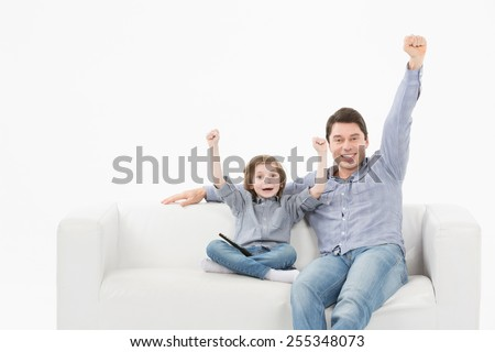 sports, happiness and people concept - smiling man and son watching sports on tv and supporting team at home - stock photo