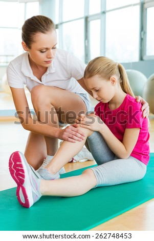 Sports injury. Frustrated little girl sitting on exercise mat and touching her injured leg while young woman consoling her  - stock photo