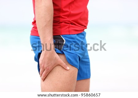 Sports injury. Running muscle stain injury in thigh. Closeup of runner touching leg in muscle pain. - stock photo