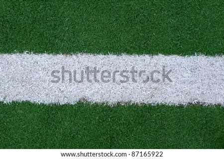 Sports lines painted on a green grassy playing field - stock photo