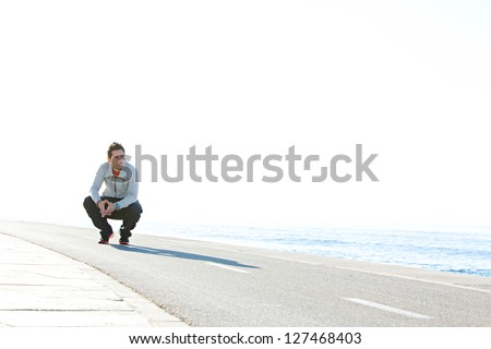 Sports man crouching down on running track by the sea, with a blue sky in the background on a sunny day, being thoughtful. - stock photo