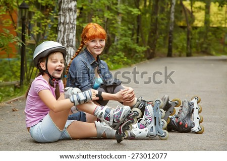 sports mother and daughter in a helmet. family on the skates. two people rollerblade. rollerskating outdoor - stock photo