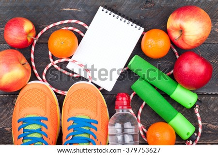 Sports shoes, jumping rope, apple, citrus, bottle of water and open blank notebook. Sport equipment. Healthy lifestyle, food, vegetarian and sport concept. Top view - stock photo