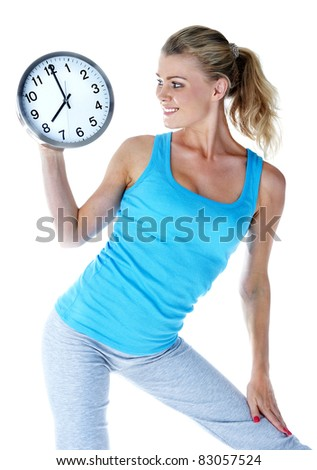 Sports time. The girl in sportswear with a big clock in hands - stock photo