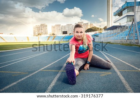 Sports woman athlete stretching her body at stadium track - stock photo