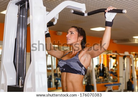 Sports woman doing exercises on power training apparatus in the gym. Pulling up on the horizontal bar. Gravitron Machine. - stock photo