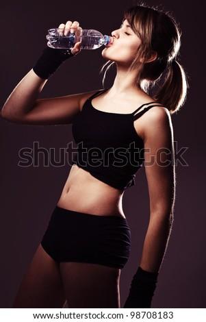 sports woman drinks water in studio - stock photo