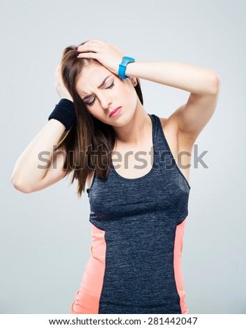 Sports woman having headache over gray background - stock photo