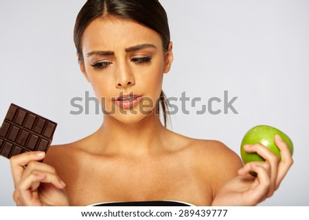 Sports woman making choice between healthy apple and unhealthy chocolate isolated on a white background. - stock photo
