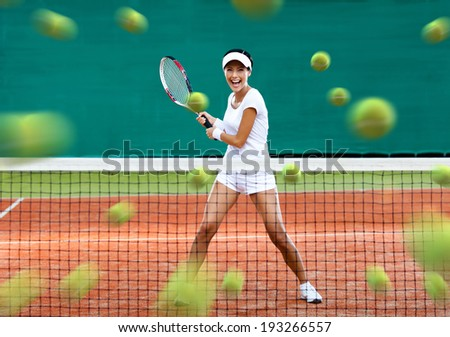 Sports woman returning lots of balls at the tennis court. Concept of tournament preparation and healthy lifestyle - stock photo