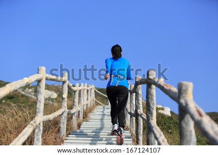 sports woman running/climbing mountain stairs - stock photo