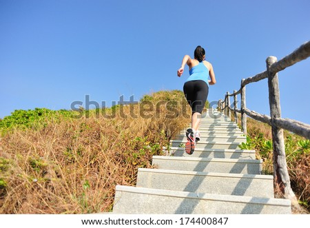 sports woman running/climbing on mountain stairs - stock photo