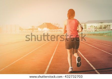 Sports woman running on tracks on sunset. Girl running from Thailand. Fitness health.  - stock photo