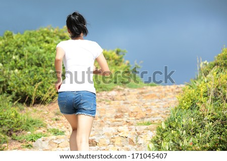 sports woman running up at mountain stairs  - stock photo