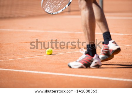 sportsman catchs up his tennis ball with racket - stock photo